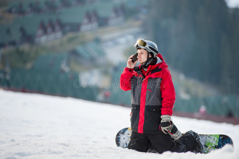 Male boarder on his snowboard at winer resort. Young snowboarder resting on ski slope, he& x27;s kneeling, looking away and talking on the phone, winter sports stock photography