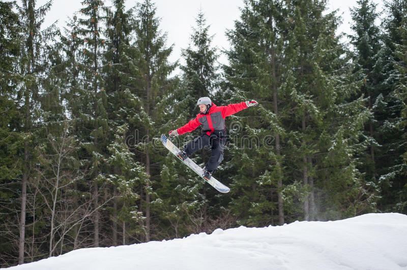 Male boarder on the snowboard jumping over the slope. Male boarder jumping and keeps one hand on the snowboard over the slope in winter with snowy slope and snow royalty free stock image