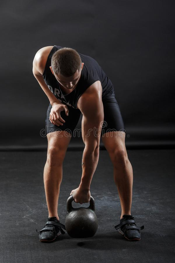 A male bodybuilder in black fitness clothes training with kettlebell stock photography
