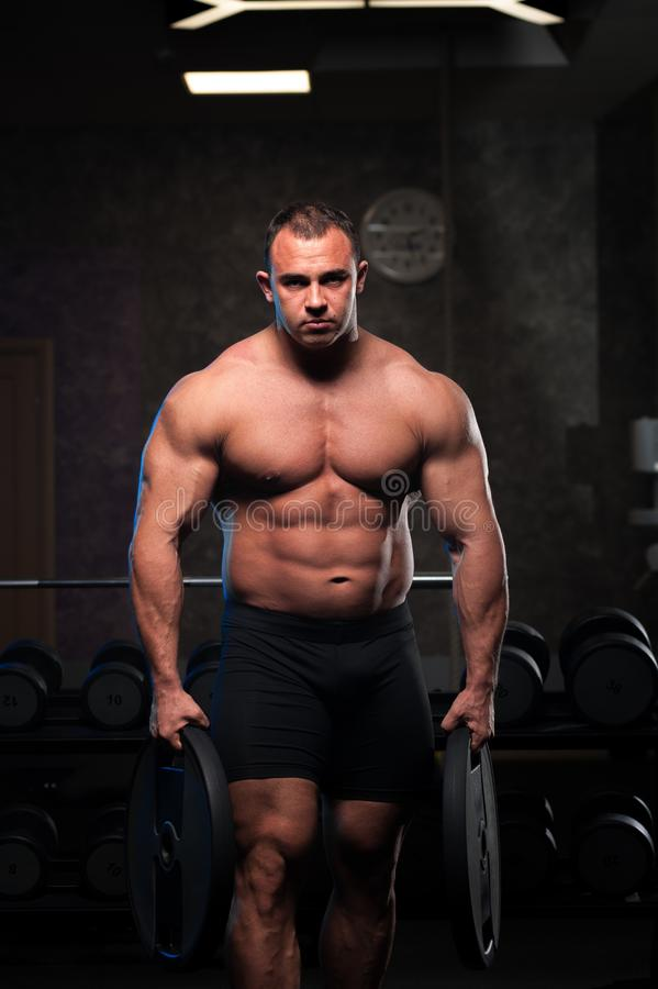 Male Bodybuilder With Naked Torso Posing In Gym Stock