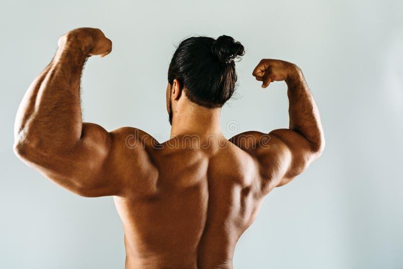 Male bodybuilder posing in studio, showing biceps stock photos