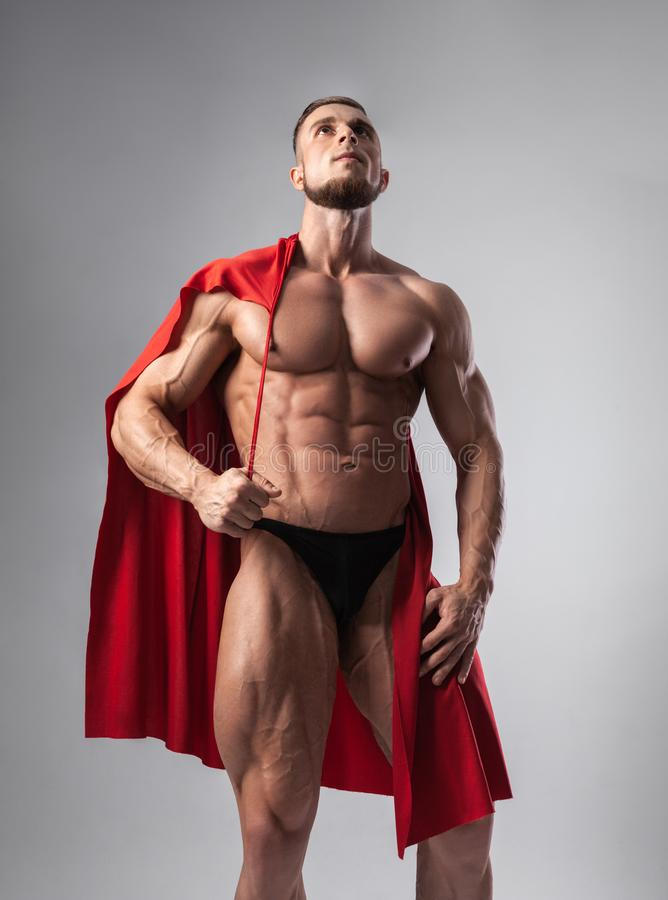 Male bodybuilder puts on his shoulders a red cloak with a serious face stock photography