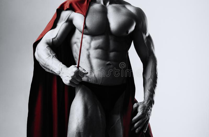 Male bodybuilder puts on his shoulders a red cloak with a serious face stock images