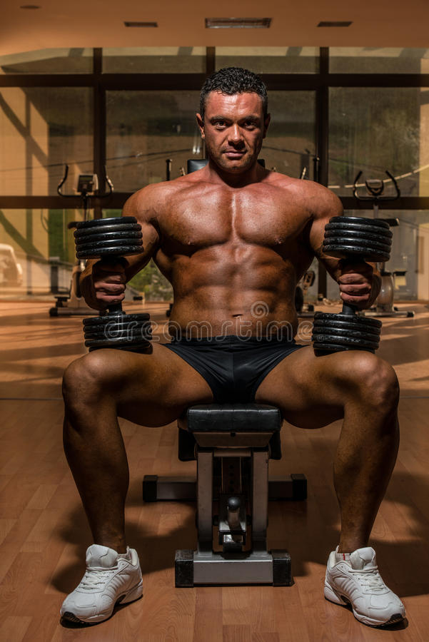 Male bodybuilder resting after doing heavy weight exercise stock images
