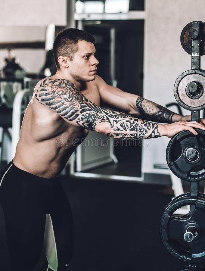 Male bodybuilder with a tattoo on his arm standing in the gym stock photography