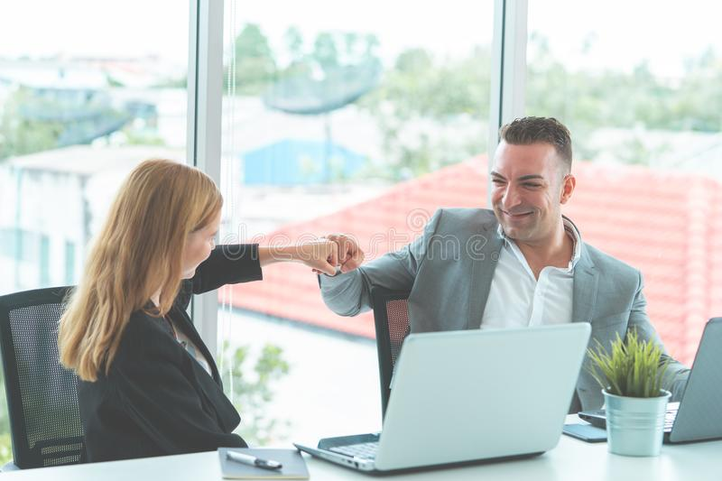 Boss fist bump with female worker for success stock photos