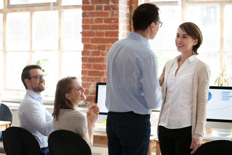 Male boss handshake female worker greeting with success. Male boss shake hand of female employee greeting with good result and promotion, excited colleagues royalty free stock image