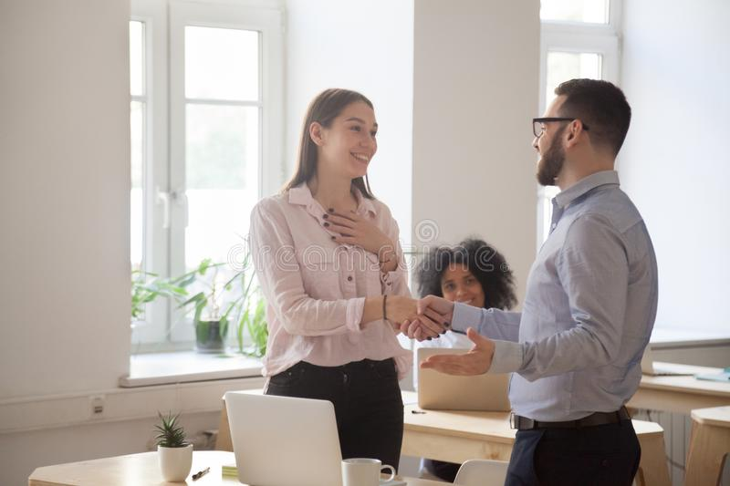 Male boss handshaking employee congratulating with promotion. Male boss congratulating female employee handshaking and greeting her on special occasion, happy royalty free stock images
