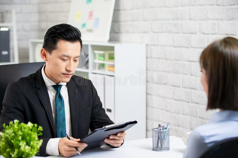 Male boss interview a woman. Asian male boss interview a women at the office stock image