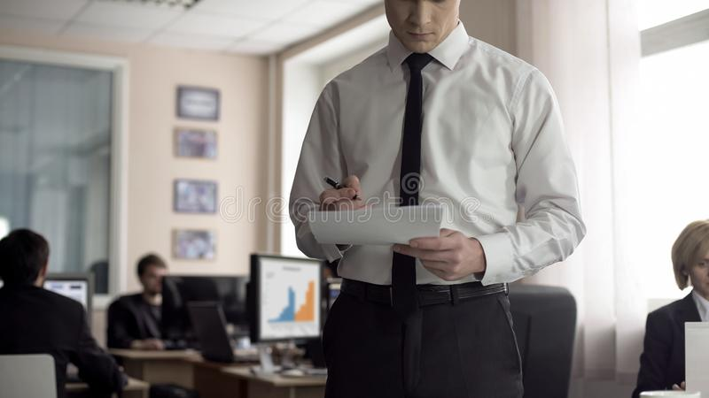 Male boss signing contract, employees working on background, busy lifestyle royalty free stock photos