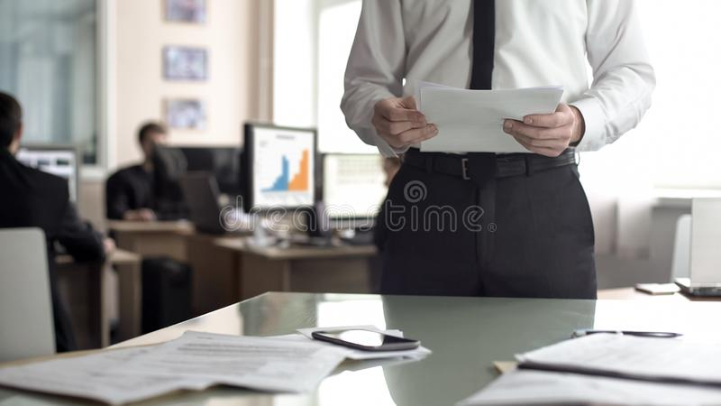 Male boss studying contract, office employees working on background, busy life. Stock photo stock photo