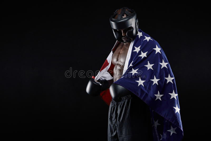 Male boxer with American flag. Portrait of young male boxer with American flag on black background. African man in boxing gear looking down stock image