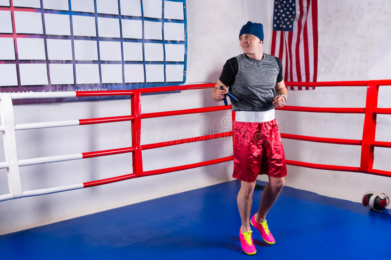 Male boxer exercising with jumping rope in a regular boxing ring royalty free stock image