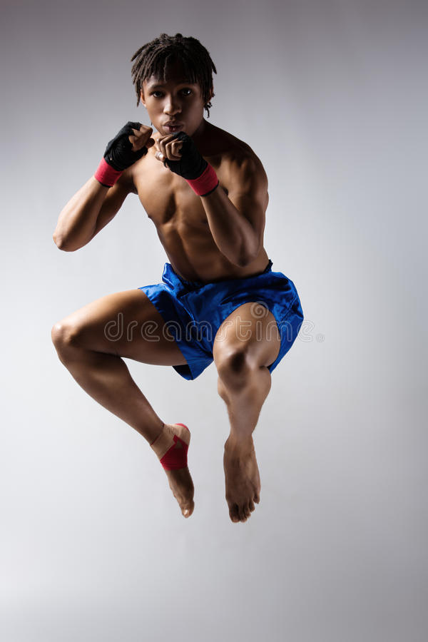 Male boxing fighter. Young muscular athletic male boxer wearing blue boxing shorts and black straps on his hands. Fighter is on a grey background stock image