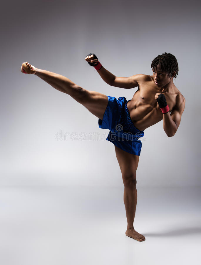 Male boxing fighter. Young muscular athletic male boxer wearing blue boxing shorts and black straps on his hands. Fighter is on a grey background stock photo