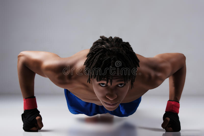 Male boxing fighter. Young muscular athletic male boxer wearing blue boxing shorts and black straps on his hands. Fighter is on a grey background royalty free stock photo