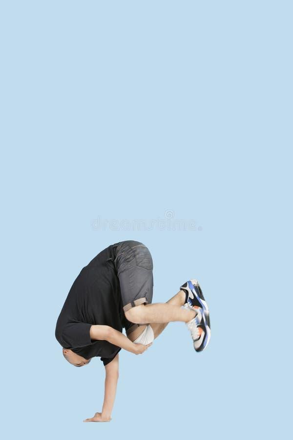 Male break dancer balances upside down on one hand over blue background stock image