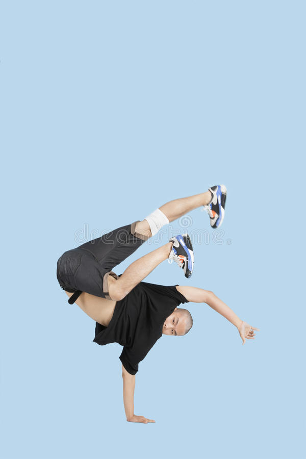 Male break dancer performing handstand over blue background royalty free stock photo