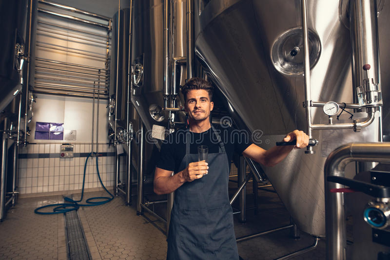 Male brewer standing by tank in brewery. Portrait of male brewer standing by tank in brewery. Man examining the beer in processing section stock photography