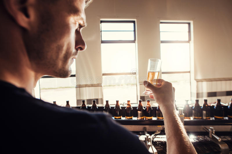 Male brewer testing craft beer at brewery factory. Young man examining the beer sample glass during manufacturing stock photo