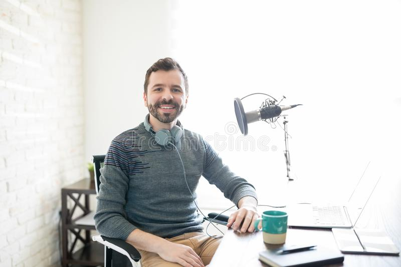 Male broadcaster at online radio station. Portrait of good looking young hispanic man sitting his desk with laptop and microphone stock photos
