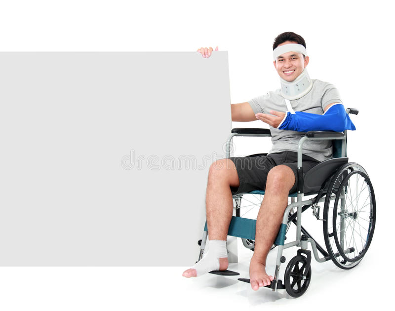 Male with broken leg sitting on the wheel chair with sign stock images