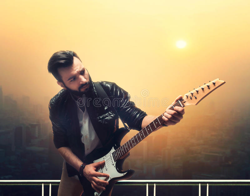 Male brutal solo guitarist with electric guitar. Against cityscape royalty free stock images