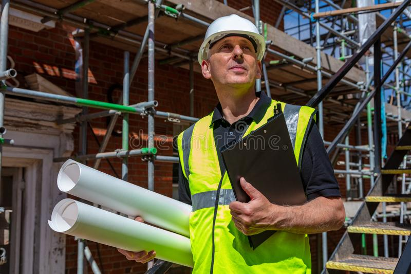 Male Builder Foreman Architect on Building Site With Clipboard and Plans stock image