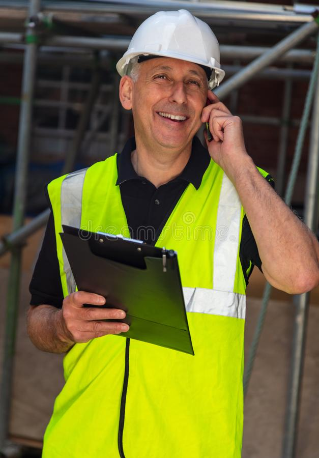 Male Builder Foreman Architect Contractor on Building Site Using Phone and Plans royalty free stock images