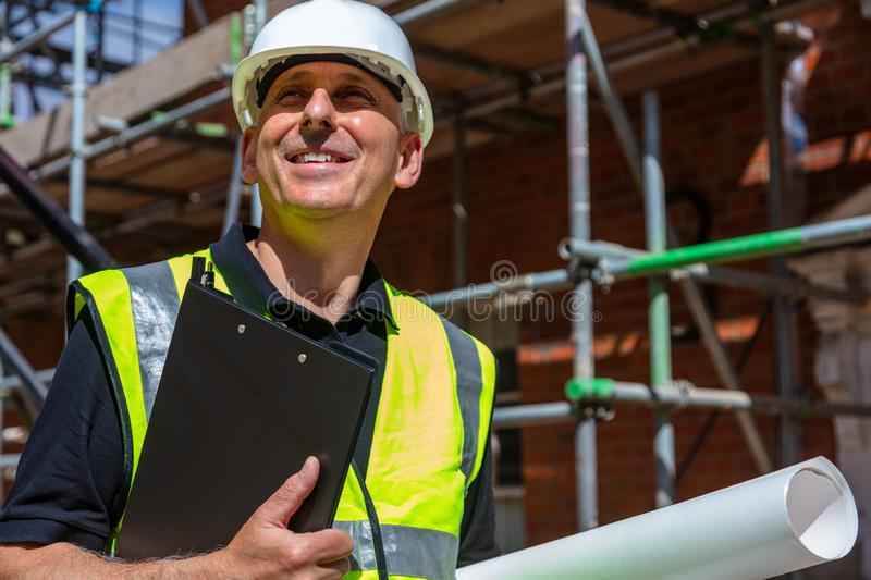 Male Builder Architect Contractor on Building Site Clipboard and Plans royalty free stock photos