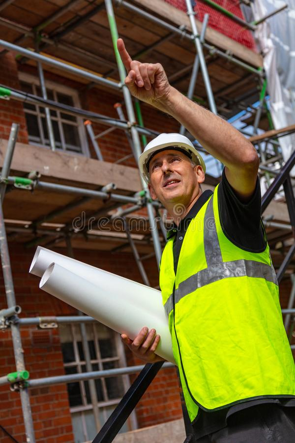 Male Builder Foreman Architect on Building Site Pointing With Plans stock image