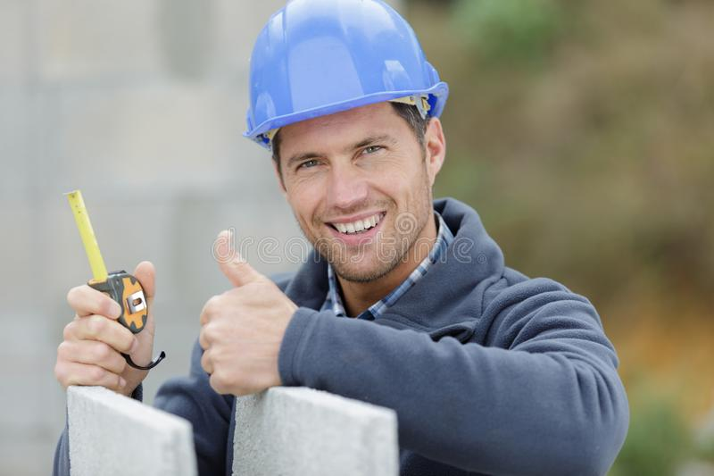 Male builder holding tape measure in hands royalty free stock photos