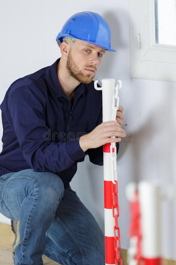 Male builder installing chains in construction site stock photos