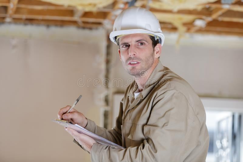 Male builder or manual worker in helmet writing on clipboard royalty free stock images