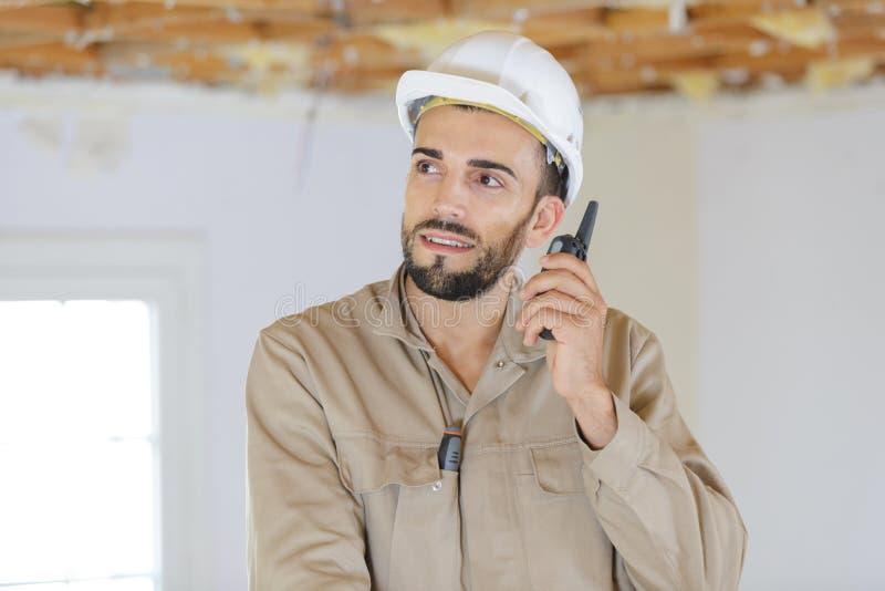 Male builder using walkie talkie indoors royalty free stock photos