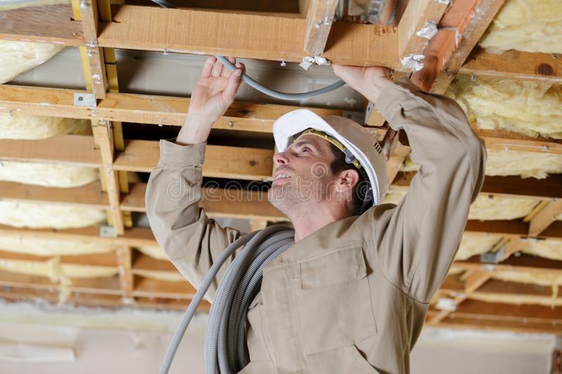 Male builder wiring inside ceiling stock images