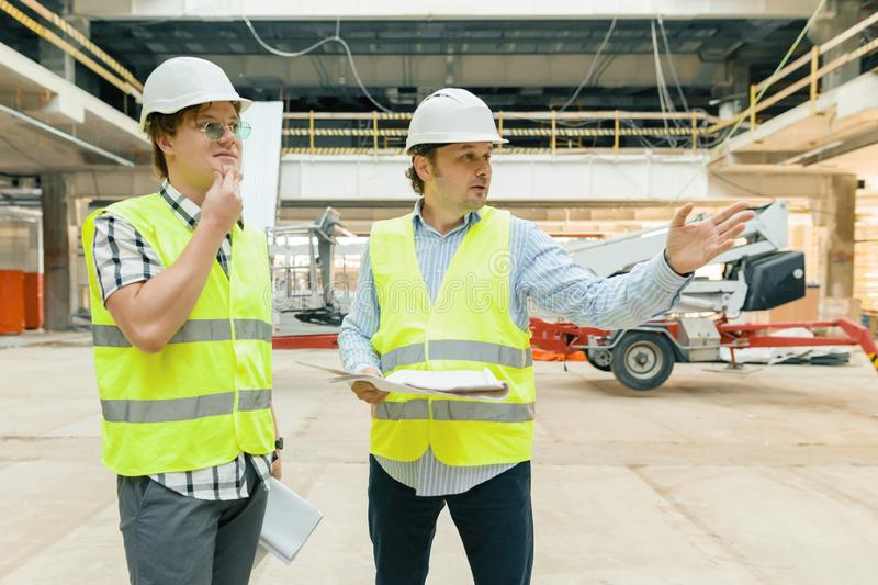 Male building workers working at construction site. Building, development, teamwork and people concept stock photography