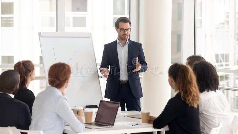 Male business coach speaker in suit give flipchart presentation. Speaker presenter consulting training persuading employees client group, mentor leader explain stock image