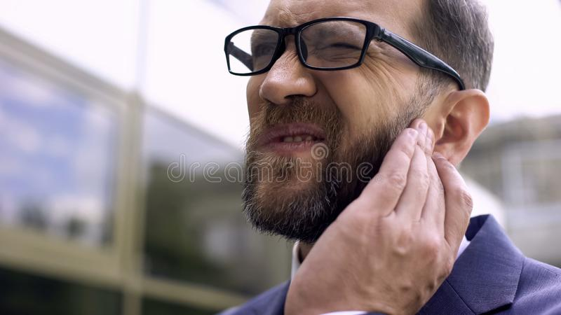 Male of business has ear pain, bacterial infection, inflammation, otitis disease. Stock photo stock image