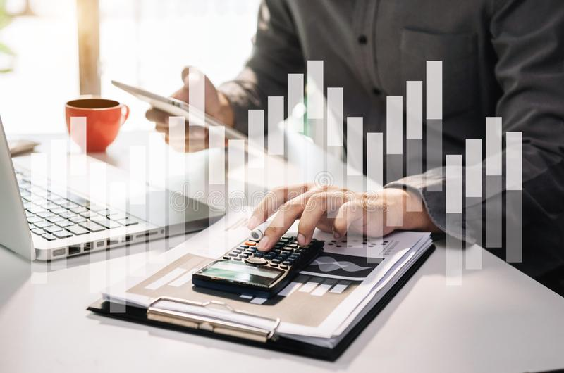 Businessman or accountant working on laptop computer with business document, graph diagram and calculator on office table royalty free stock photography