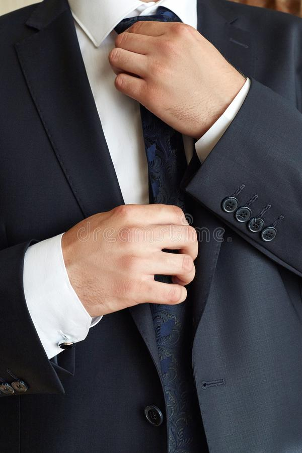 Male businessman corrects a tie. Successful Manager wears a tie. stock photo
