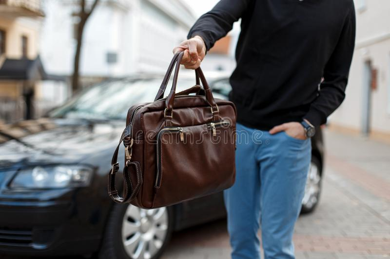 Male businessman giving away leather bag on background of car. stock image