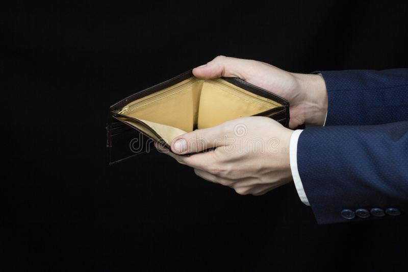 Male businessman holding a blank purse on his arms outstretched, close-up, black background stock image