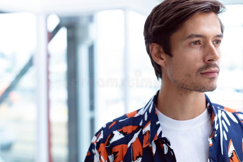 Male businessman looking away in a modern office. Front view of young Caucasian male businessman looking away in a modern office stock photography