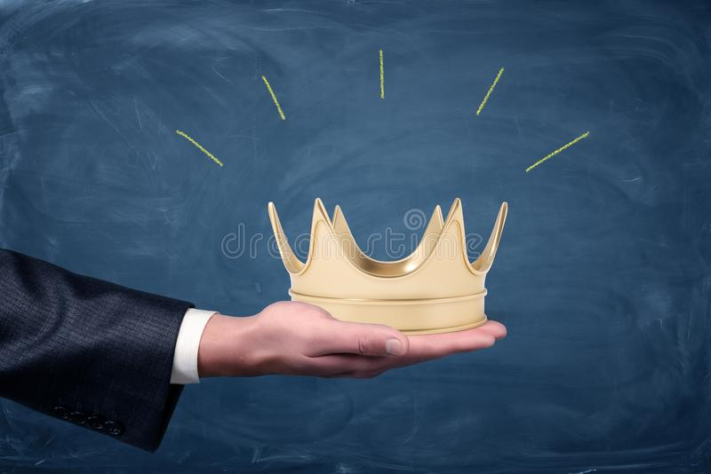 A male businessman`s hand holding a golden crown on an open palm. Invitation to fist class. stock image