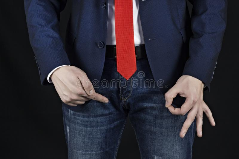 Male businessman showing gesture class at inguinal area, erection and Viagra, black background, viagra, royalty free stock photos