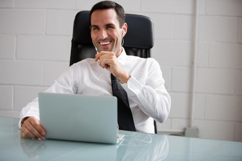 Male businessman talking with earphones. Half length portrait of a male businessman with laptop computer talking with earphones stock image