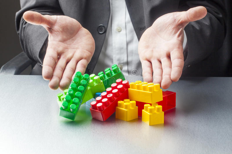 Male businessman using kids toys for building business stock image