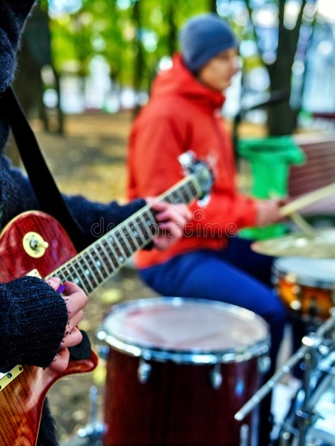 Male buskers on autumn outdoor play guitar. Cool weather royalty free stock photo