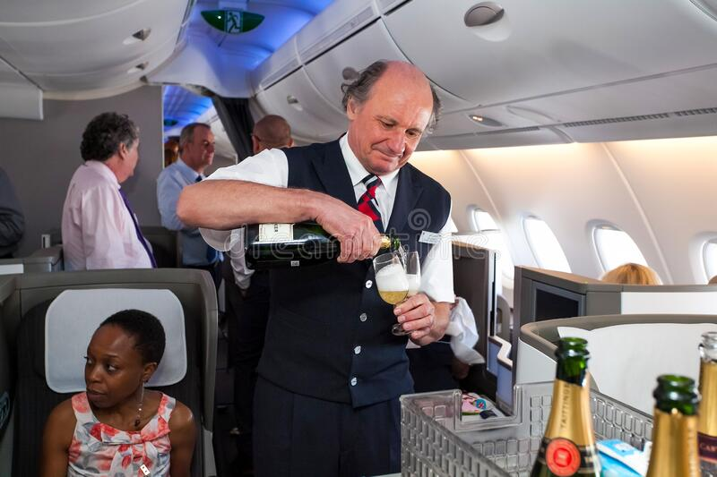 Male cabin crew pouring a glass of Champaign in business class of an Airbus A380. Johannesburg, South Africa - February 06, 2014: Male cabin crew pouring a glass stock photography